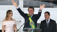 Jair Bolsonaro waves to supporters flanked by First Lady Michelle Bolsonaro (L) and Brazil's new Vice-President Hamilton Mourao, during their inauguration ceremony   Source: Getty Images)