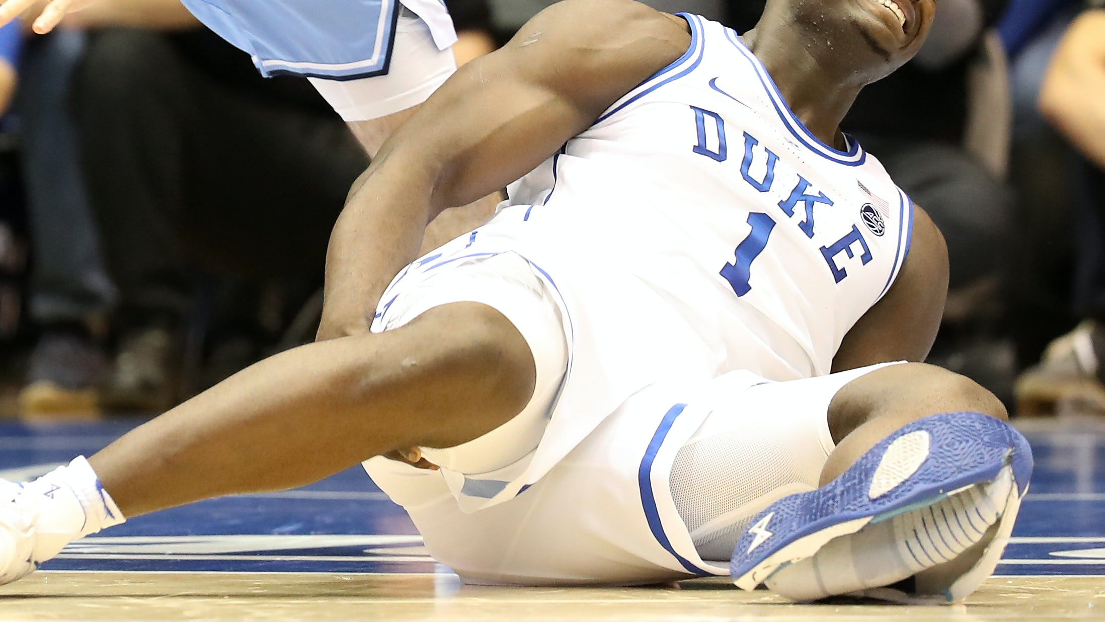 Zion Williamson of the Duke Blue Devils reacts after falling as his shoe breaks against Luke Maye of the North Carolina Tar Heels during their game on February 20, 2019 in Durham, North Carolina. | Photo by Streeter Lecka/Getty Images
