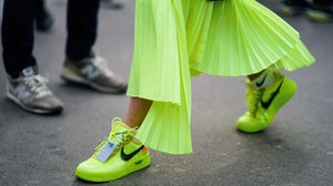PARIS, FRANCE - FEBRUARY 28: A guest wears a neon green asymmetric pleated skirt, white Nike ankle socks, neon green Nike sneakers, outside Ann Demeulemeester, during Paris Fashion Week Womenswear Fall/Winter 2019/2020, on February 28, 2019 in Paris, France. (Photo by Edward Berthelot/Getty Images)