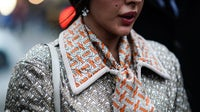 A guest wears a Burberry jacket and monogram scarf at London Fashion Week | Source: Edward Berthelot/Getty Images