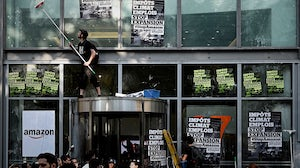 People glue placards on the frontage of the Amazon France offices during a blockade  organized by the NGO Amis de la Terre, in Clichy, on the outskirts of Paris | Source: Getty Images