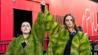 Activists from Extinction Rebellion wear coats made of living grass during a demonstration outside. | Source: Getty Images