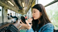 A woman applying makeup on the Japanese metro | Source: Shutterstock