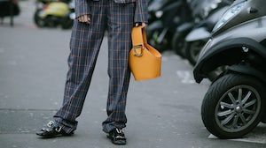 Cedric Charlier show attendee with a Danse Lente bag by Vanni Bassetti | Source: Getty Images