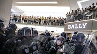 Riot police stand off against demonstrators in front of a Bally store inside New Town Plaza shopping mall | Source: Getty Images