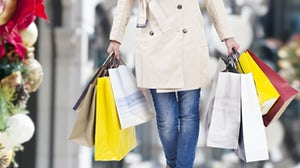 Consumer walking with Christmas shopping bags | Source: Shutterstock