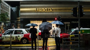 Pedestrians in front of a Prada store in the central district of Hong Kong, China | Source: Getty Images