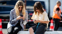 Veronika Heilbrunner and Natasha Goldenberg on their phones at Paris Fashion Week | Source: Getty Images