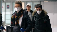 Travellers wearing protective masks at Charles De Gaulle | Source: Chesnot/Getty Images
