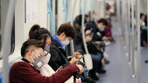 People wearing surgical mask sitting in subway in Shanghai. | Shutterstock