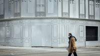 A pedestrian passes hoardings covering a Dior store in Paris.   Source: Cyril Marcilhacy/Bloomberg via Getty Images