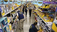Employees restock shelves of school supplies at a Walmart store | Source: Getty Images
