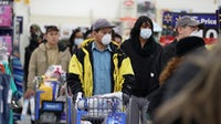 People wearing masks and gloves wait to checkout at Walmart | Source: Getty Images