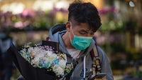 A shopper carries flowers for Valentine's Day wearing a face mask as a preventative measure against Covid-19   Source: Getty Images
