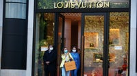 Shoppers leaving the Louis Vuitton store on the Champs-Élysées in Paris this month   Source: Getty Images