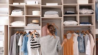 A person choosing outfit from large wardrobe closet | Source: Shutterstock