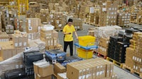 A worker transports express boxes at a logistic base of Suning.com Co., Ltd. before the upcoming 618 Shopping Festival in 2019 | Source: Getty Images