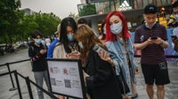 Shoppers scan their local health QR codes from the Beijing Municipality to show security before entering a shopping area during the May holiday on May 3, 2020 in Beijing, China | Source: Getty Images