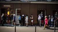 Customers line up in a queue in front of an Hermès store in Paris | Source: Getty Images