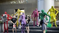 Shoppers and pedestrians pose for photographs with sculptures outside a Prada SpA luxury fashion store on Orchard Road in Singapore | Source: Getty Images