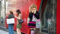 Shoppers look at their smartphones in the Harajuku district of Tokyo | Source: Getty Images