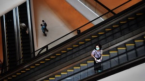 A woman wears a facemask in a shopping mall| Source: Getty Images