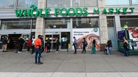 Customers waiting in line outside of Whole Foods | Source: Getty Images