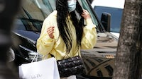 A masked woman in Paris carries bags from Baby Dior and Bottega Veneta.