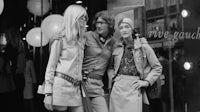 Designer Yves Saint Laurent with models Betty Catroux and Loulou de la Falaise | Source: Getty Images