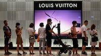 Customers wait in line to enter a Louis Vuitton shop in Wuhan | Source: Getty Images