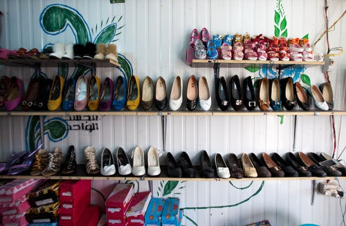 Rows of shoes against a caravan wall | Photo: Dustin Mennie